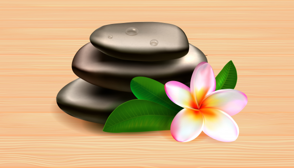 Spa stones with green leaves and tropical flower on wooden table against grey background.